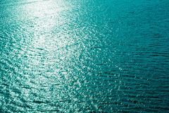 Clear blue water with sun reflections background Royalty Free Stock Photo
