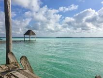 The clear-blue waters of Lago Bacalar in Mexico. View from a dock over the clear-blue waters of Lago Bacalar in Mexico Stock Photo