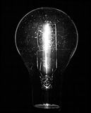 Clear Bulb with Filament. Clear glass light bulb is isolated on black background.  Light is on and the filament is visible as well as some specks of dust on Royalty Free Stock Photo