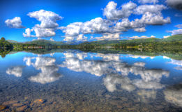 Clear calm peaceful water with cloudscape and cloud reflections in summer HDR Royalty Free Stock Image