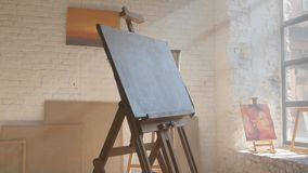Clear canvas on wooden easel ready to be painted in art workshop. White clear canvas on wooden easel ready to be painted on, paintings on the stretchers and stock video
