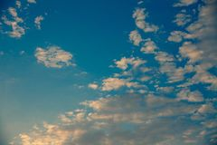 Clear cloudy sky with sunset light. Different shades of blue colors and white clouds. Beautiful background. Day ending. Relaxing t. Clear cloudy sky with sunset royalty free stock photography