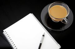 Clear cup of coffee with notebook Stock Image