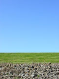 Clear day. A view of the sky on a clear day with green grass and rocks in the foreground Stock Image