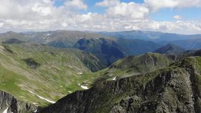 View over The Fagaras Mountains - Romania. Clear day. Clear Day. Cloudy. Mid day. Summer. Snow surfaces are visible. Rocky areas.  Fagaras Mountains - Romania stock video