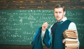 Clear explanation. Teacher formal wear and glasses looks smart, chalkboard background. Man in end of lesson takes off. Eyeglasses. Teacher finished explanation stock photo