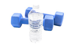 Clear full water bottle and ywo blue dumbell weights isolated on Stock Images