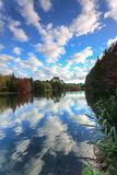 Reflections of fluffy clouds and autumn foliage in a lake royalty free stock photo