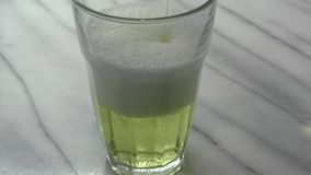 Clear glass being filled with Lime fizzy drink stock video footage