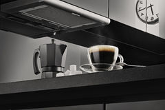 Clear Glass Coffee Cup With Black Coffee on Black Kitchen Top Beside Black Coffee Maker Royalty Free Stock Photo