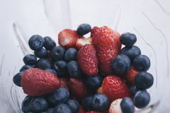 Clear Glass Container Containing Blue Berries and Strawberries Stock Image