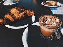 Clear Glass Cup Filled With Cappuccino Beside Croissant Bread Royalty Free Stock Photos