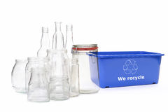 Clear glass disposal. Clear glass jars and bottles and blue plastic disposal bin with white recycle symbol over white stock image