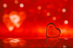 Clear glass heart on red  glitter background Stock Photos