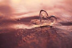 Clear glass heart on  sand beach with sunrise sun light Stock Photos