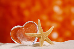 Clear glass heart with starfish. On white sand beach, and red glitter backdrop royalty free stock images
