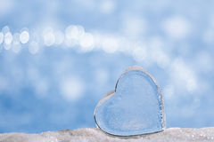 Clear glass heart on white  glitter and blue background Stock Photos