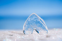 Clear glass heart on white  glitter and blue background Royalty Free Stock Photo