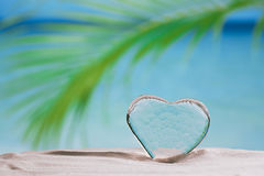 Clear glass heart on white sand beach Stock Images