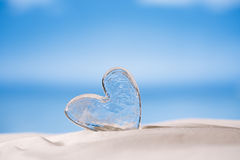 Clear glass heart on white sand beach Stock Image