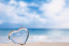 Clear glass heart on white sand beach Stock Photos