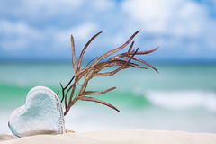 Clear glass heart on white sand beach Royalty Free Stock Photography