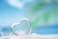 Clear glass heart on white sand beach Stock Photo