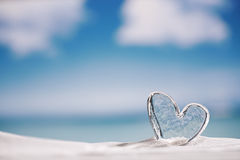 Clear glass heart on white sand beach Royalty Free Stock Photo