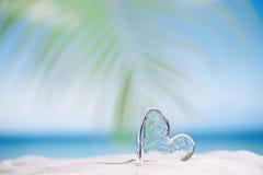 Clear glass heart on white sand beach Royalty Free Stock Photos