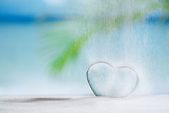 Clear glass heart on white sand beach Royalty Free Stock Images