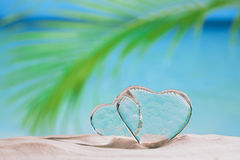 Clear glass hearts on white sand beach Stock Photo