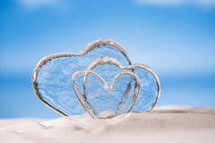 Clear glass hearts on white sand beach Stock Images