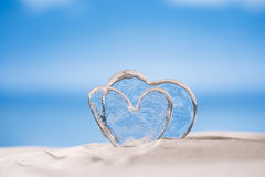 Clear glass hearts on white sand beach Royalty Free Stock Images