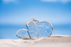 Clear glass hearts on white sand beach Stock Photography
