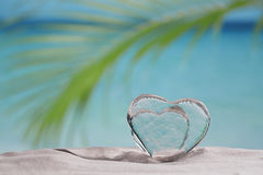 Clear glass hearts on white sand beach Royalty Free Stock Image