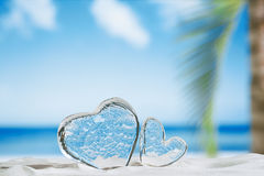 Clear glass hearts on white sand beach Stock Image
