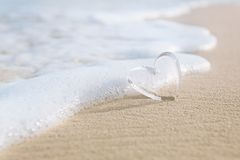 Clear glass hearts on white sand beach, Stock Photos