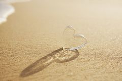 Clear glass hearts on white sand beach, Stock Image