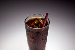 Clear glass with ice and soda with red straw. Shot against gradient background, glass dripping with droplets of water, seen from the top, cropped close Royalty Free Stock Image