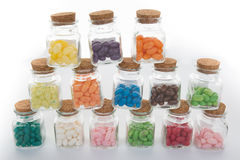 Clear glass jar of candy and colorful jelly beans spilled from jar Royalty Free Stock Images