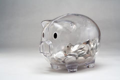 Clear Glass Piggy Bank. Childs clear piggy bank with coins Royalty Free Stock Image