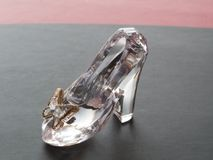 Clear glass slipper for doll isolated on black background royalty free stock photography