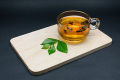 Clear glass of tea and tea leaves on wooden plate. Clear glass of tea and tea leaves on wooden plate  on black background Royalty Free Stock Photo