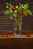 Clear glass vase with bunch of ripe red wild strawberries Royalty Free Stock Photos