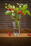 Clear glass vase with bunch of ripe red wild strawberries Royalty Free Stock Image