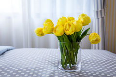 Clear glass vase containing cut yellow tulips and clear glass. Baubles against a background bedroom and curtain daylight time Stock Photos