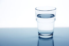 Clear glass of water on a white background. In blue colour Stock Image