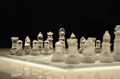 Clear Glass and White Chess Piece on White Chess Board With Black Background Stock Image