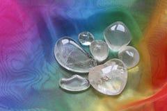 Clear healing crystals on rainbow chiffon. Bright clear healing quartz crystals on rainbow colored chiffon material Royalty Free Stock Photos