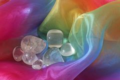 Clear Healing Quartz Crystals. Seven Clear Quartz tumbled gemstones on a floaty folding Rainbow Chiffon Material Background Royalty Free Stock Photography